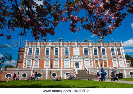 Croxteth Hall, Liverpool, UK 5 May 2018. UK Weather Croxteth Hall, Liverpool England UK 05/05 2018 People enjoying walking their children at Croxteth Hall in the Spring sunshine on the Bank Holiday Mayday Weekend at Croxteth Hall, View of Croxteth Hall from underneath a Spring blooming blossom tree Croxteth Country Park, Liverpool England UK Parts of Peaky Blinders were filmed here. Credit: Christopher Canty Photography/Alamy Live News - Stock Photo