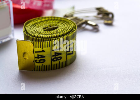 Measuring tape with pins on blurred background. Sewing tools - Stock Photo