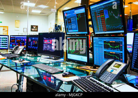 Computer screens on desk showing charts and data analyses - Stock Photo