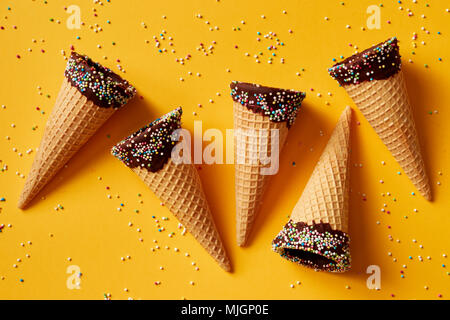 Ice cream cone with colorful sprinkles on yellow background. - Stock Photo