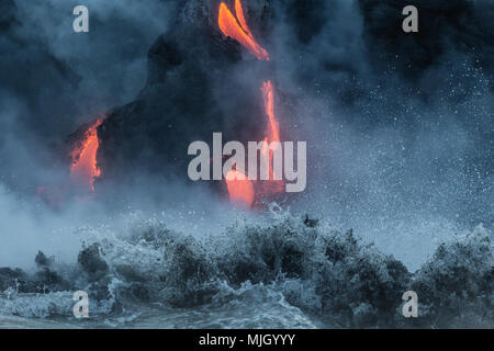 Streams of lava pour into the Pacific Ocean from Kilauea Volcano outside Volcanoes National Park. - Stock Photo