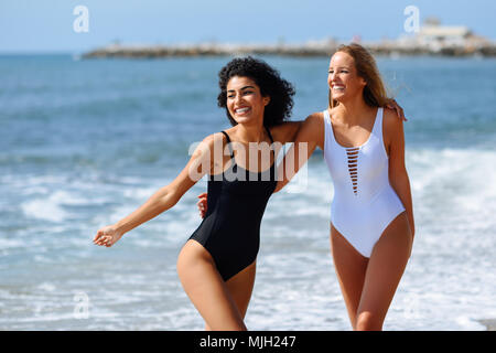 Two young women with beautiful bodies in swimwear on a tropical beach. Funny caucasian and arabic females wearing black and white swimsuits walking al - Stock Photo