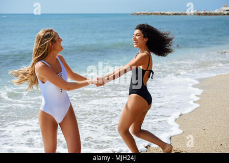 Two young women with beautiful bodies in swimwear having fun with their hands caught on the beach. Funny caucasian and arabic females wearing black an - Stock Photo
