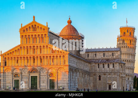 Golden sunlight hit on the top of the Leaning Tower and Pisa Cathedral in Italy at sunset - Stock Photo