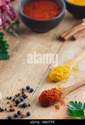 Wood spoon filled with paprika on rustic wood table. Various ingredients on table. - Stock Photo