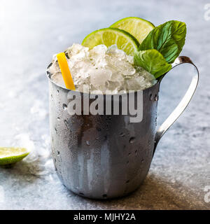 Moscow Mule Cocktail with Lime, Mint Leaves and Crushed Ice in Metal Cup. Summer Beverage. - Stock Photo