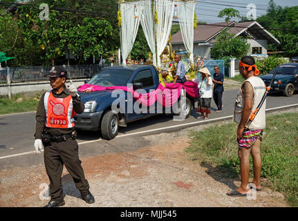 Songkran Thai New Year, policeman controls traffic for pickup truck carrying golden Buddha statue, monk and decorations, Udon Thani, Isaan, Thailand - Stock Photo