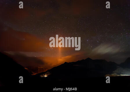 Night sky with stars, illumination from the city and traces of headlights on the road in the mountains - Stock Photo