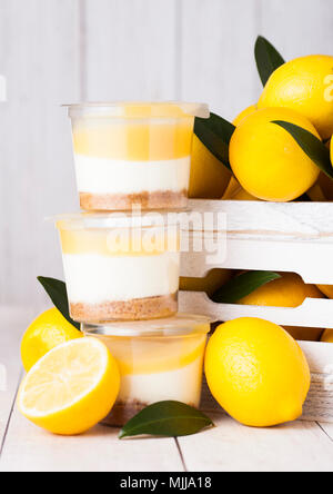 Plastic cup with lemon cream and biscuit dessert with raw lemons in white wooden box - Stock Photo