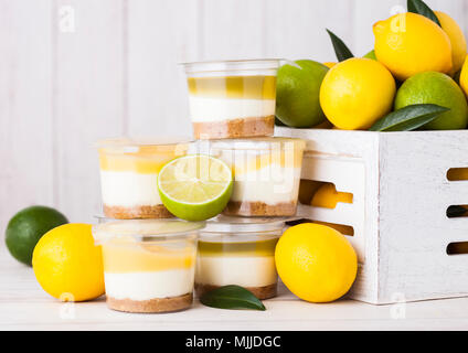 Plastic cup with lemon lime cream and biscuit dessert with raw lemons in white wooden box - Stock Photo