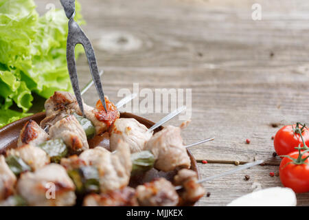A fork stuck in tender meat cooked on an open fire. Juicy kebabs. Still-life on a wooden background. Rustic. Close-up. - Stock Photo