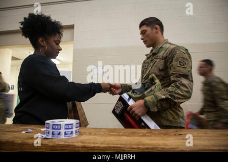 U.S. Army paratrooper gives his toy to receive his lottery ticket for the 20th Annual Randy Oler Memorial Operation Toy Drop, hosted by U.S. Army Civil Affairs & Psychological Operations Command (Airborne), Dec. 01, 2017 at Pope Air Field, North Carolina. Operation Toy Drop is the world's largest combined airborne operation with eight partner nation paratroopers participating and allows Soldiers the opportunity to train on their military occupational specialty, maintain their airborne readiness, and give back to the local community. (U.S. Army photo by Spc. Jesse L. Artis Jr./Released) - Stock Photo