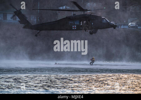 A U.S. Army UH-60 Blackhawk from the West Virginia National Guard's Charlie Co., 2/104th General Support Aviation Battalion, hovers over the Kanawha River during a mock extraction in Dunbar, W.Va. Dec. 2, 2017. Members of the WVSWRT conducted swift water rescue training on the Kanawha River to hone their skills and practice as a cohesive team. (U.S. Air National Guard photo by Capt. Holli Nelson) - Stock Photo
