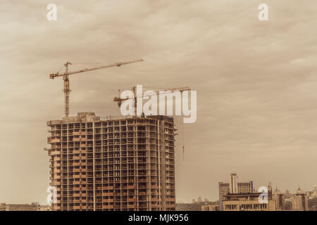 Building cranes and building under construction stylized photo. - Stock Photo