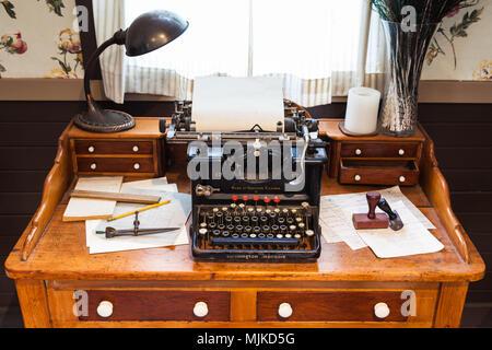 Antique Remington typewriter on an old wooden desk - Stock Photo