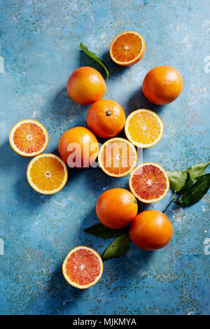 Blood oranges whole and sliced on a blue surface (seen from above). - Stock Photo