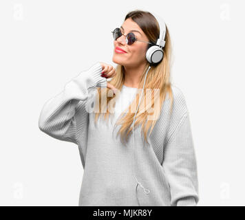 Young woman listen to music with headphone proud, excited and arrogant, pointing with victory face - Stock Photo