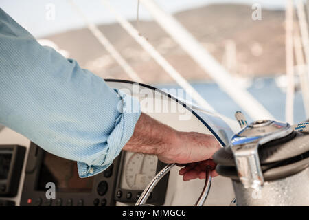Close-up image of a man's hand on throttle control of a boat - Stock Photo