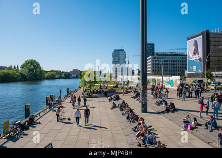 Berlin, Germany - may, 2018:  Many people at river Spree at Berlin Wall ( East Side Gallery) on a sunny day in Berlin, Germany - Stock Photo
