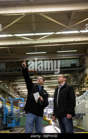 Scott Evertsen, the Arsenal's energy manager, right, discussing with contract representative Joseph LaVigne about the scope of the contract that will reduce energy costs by replacing hundreds of vapor and fluorescent lights in the manufacturing centers with LED lighting. - Stock Photo