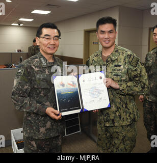 171221-N-TB148-005 BUSAN, Republic of Korea (Dec. 21, 2017) Republic of Korea (ROK) Navy Vice Adm. Jung, Jin-Sup, commander, ROK Fleet, presents Lt.  Sean Jin with a letter of appointment for his selection to the 'Great Young Minds' Junior Officers' Engagement and Cooperation Program. The 'Great Young Minds' initiative brings together hand-selected, young officers from the ROK and U.S. navies and challenges them to develop innovative solutions to further enhance the ROK -U.S. alliance of the future. (U.S. Navy photo by Mass Communication Specialist Seaman William Carlisle) - Stock Photo