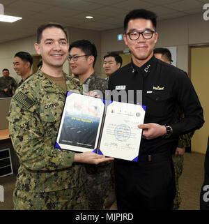 171221-N-TB148-047 BUSAN, Republic of Korea (Dec. 21, 2017) Rear Adm. Brad Cooper, commander, U.S. Naval Forces Korea (CNFK), presents Lt. Yu, Jin Hong with a letter of appointment for his selection to the 'Great Young Minds' Junior Officers' Engagement and Cooperation Program. The 'Great Young Minds' initiative brings together hand-selected, young officers from the ROK and U.S. navies and challenges them to develop innovative solutions to further enhance the ROK -U.S. alliance of the future. (U.S. Navy photo by Mass Communication Specialist Seaman William Carlisle) - Stock Photo