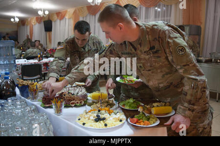 Yavoriv, Ukraine – 27th Infantry Brigade Combat Team Soldiers assigned to the Joint Multinational Training Group – Ukraine host a Christmas dinner at the Yavoriv Combat Training Center near Yavoriv, Ukraine. Currently more than 220 of the Brigade's Soldiers are deployed overseas working alongside the Ukrainian Army. (U.S. Army photo by Sgt. Alexander Rector) - Stock Photo