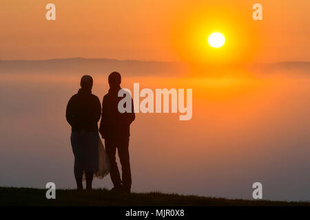 Glastonbury, Somerset, UK.  6th May 2018. UK Weather.   Visitors view the sunrise which is rising over a layer of mist from the top of the hill at Glasonbury Tor in Somerset.  Picture Credit: Graham Hunt/Alamy Live News - Stock Photo