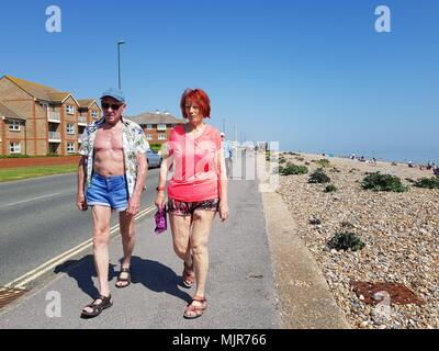 A couple enjoying an afternoon stroll along the seafront road on a hot and sunny day during the Spring 2018 heatwave, on the South Coast in the UK. - Stock Photo