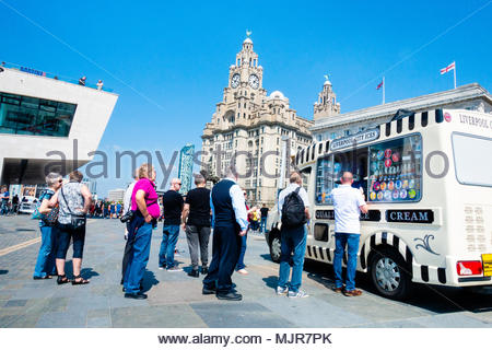 Pier Head in Liverpool, on the banks of the River Mersey, people queue to buy an Ice Cream to col down on the unusually hot day, in front of the Liver Building, on a sunny Bank Holiday Weekend, Liverpool, England UK Europe - Stock Photo