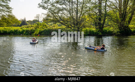 Two boys floating in dinghies and playing with a ball on the River Avon Fordingbridge, New Forest, Hampshire, UK - Stock Photo