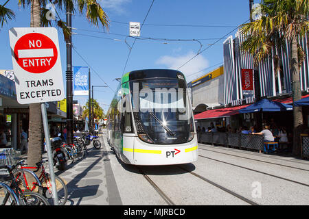 Melbourne, Australia: April 07, 2018: A tram leaves Acland Street tram stop in St Kilda. Only trams are allowed the full length of Acland Street. - Stock Photo