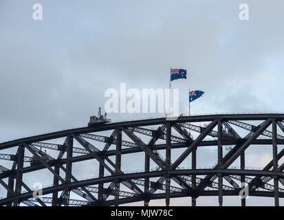Sydney,NSW,Australia-December 7,2016: Top portion of the Sydney Harbour Bridge with flags under an overcast sky in Sydney, Australia - Stock Photo