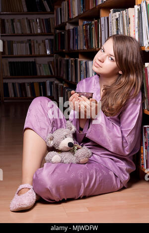 The girl in purple pajamas with a toy sits on a shelf of books in the library of photography - Stock Photo