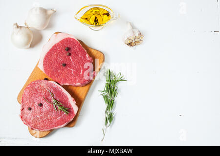 Raw meat with olive oil, spices and rosemary on white wooden board. Fresh beef. Ready to roasting. - Stock Photo