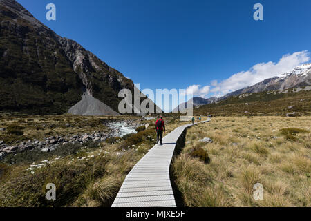 MOUNT COOK, NEW ZEALAND - NOVEMBER 18, 2017: Hikers walking on a boardwalk on the famous Hooker Valley Track amongst alpine scenery in the Mount Cook  - Stock Photo