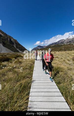 MOUNT COOK, NEW ZEALAND - NOVEMBR 18, 2017: Hikers walking on a boardwalk on the famous Hooker Valley Track amongst alpine scenery in the Mount Cook A - Stock Photo