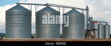 Silos. Storage and drying of grains, wheat, corn, soy, sunflower against the blue sky. Panorama. - Stock Photo