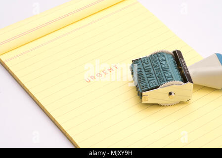 'Urgent' rubber stamp with yellow note pad - Stock Photo