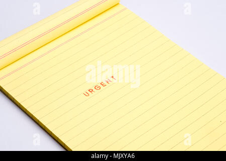 'URGENT' rubber stamp on yellow note pad. - Stock Photo