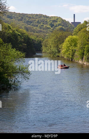 The River Severn from the Jackfield Bridge in Ironbridge, Shropshire, England, with the towers of Ironbridge Power Station and tourists on a boat. - Stock Photo