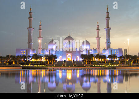 Sheikh Zayed Grand Mosque in Abu Dhabi, capital city of the United Arab Emirates. Mosque is built from Italian white marble. Reflection in lake - Stock Photo