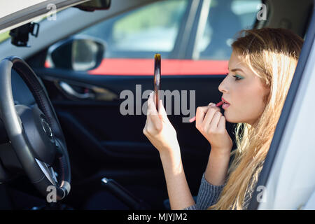 Young blonde woman applying lipstick looking at mirror in her car. Girl making-up herself in urban background. - Stock Photo