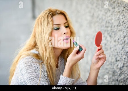 Young blonde woman applying lipstick looking at mirror in the street. Girl making-up herself in urban background using pink lipstick. - Stock Photo