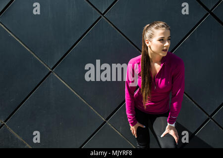 Young sporty girl wearing pink sportswear stretching arms near black wall preparing for working out, outdoor training, warming up after or before fitn - Stock Photo