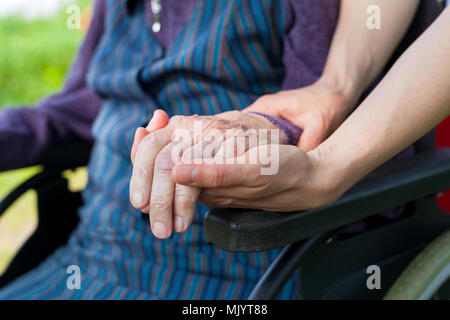 Close up picture of carer holding elderly woman's shaking hands, sitting in a wheelchair - Parkinson disease - Stock Photo