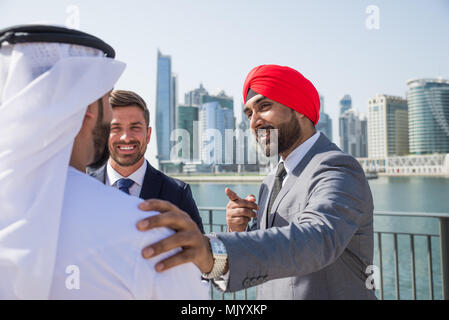 Multiethnic business team meeting outdoors - Three businessmen talking about business on a formal meeting - Stock Photo