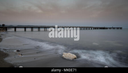 Seascape with jetty during a dramatic cloudy sunset at Polis town area in Paphos, Cyprus - Stock Photo