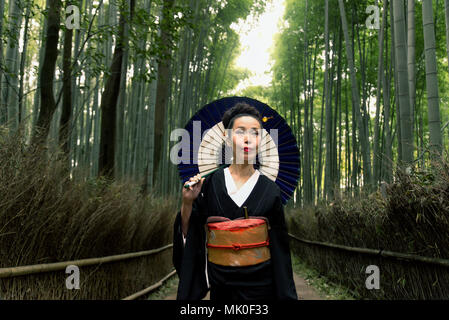 Asian woman wearing japanese traditional kimono at Bamboo Forest in Kyoto, Japan - Stock Photo