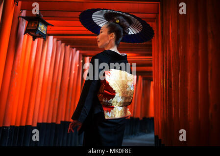 Asian woman in traditional japanese kimonos at Fushimi Inari Shrine in Kyoto, Japan - Stock Photo